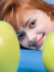 Jolly teen redhead poses naked with apples demonstrating the most intimate parts of her body.