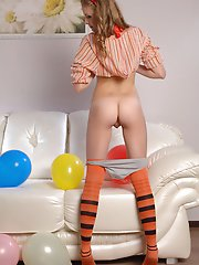 Beautiful shapely teen honey with colorful balloons taking off her clothes on the sofa.