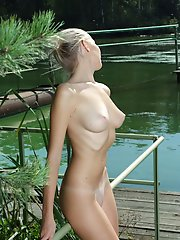 Gorgeous beauty poses naked by the river flaunting her amazing c cup tits and perfect ass.