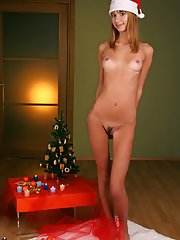 Lovely teen in Christmas hat, but fully nude, sits on the floor and entertains with many-coloured Christmas balls.
