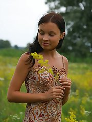 Tremendous striking teen is having a walk in the birch forest and lolls about in the flower valley without any article of clothes.